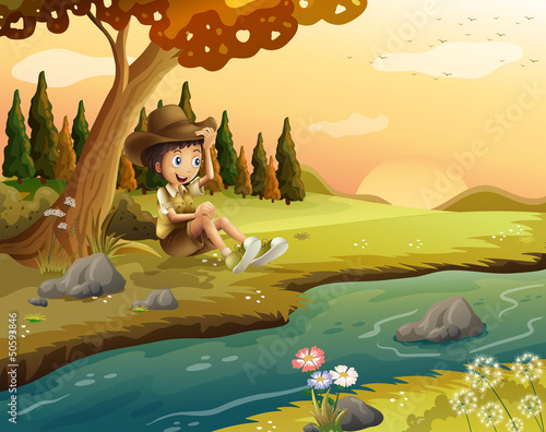 A boy sitting at the riverbank