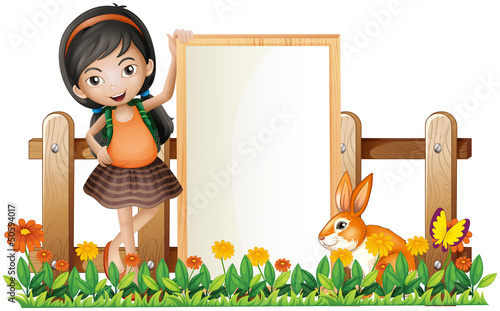 A girl standing beside an empty frame with a bunny