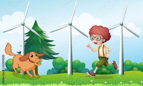Foto op Canvas Honden A boy playing with his dog near the windmill