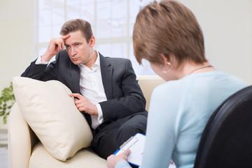 Depressed man talking with psychologist