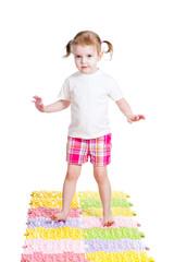 little girl massaging her feet on mat