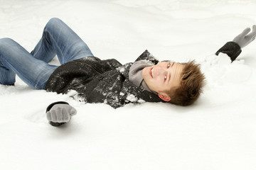 Young handsome man lying on snow.