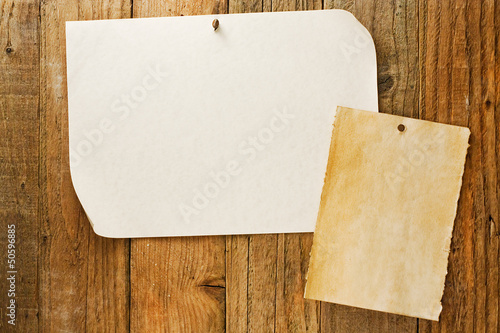 mottled beige paper naled to distressed wooden wall