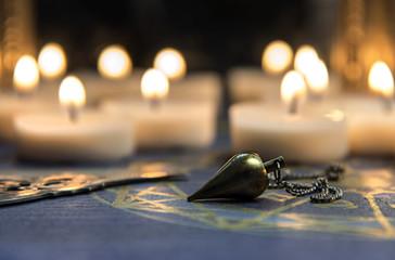 Pendel im Halbdunkel vor vielen Kerzen