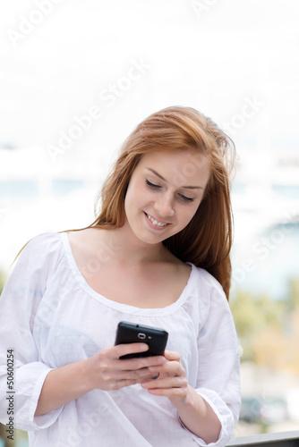junge frau schaut auf ihr smartphone