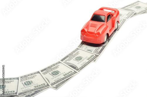 Toy car moving on a US paper currency road