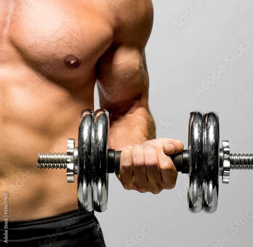 powerful muscular man lifting weights - 50601460