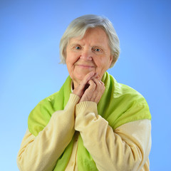 Senior happy woman with grey hairs against blue background.