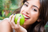 Portrait of a young woman's face eating an apple - 50603411