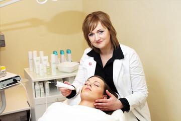 Kosmetikerin bei einer Gesichtsbehandlung