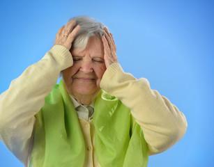 Senior worried woman against blue background.