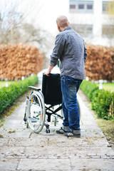 Mann schiebt Rollstuhl