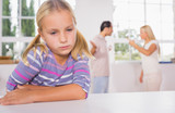 Little girl looking sad in front of fighting parents