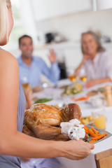 Woman bringing the turkey to the dinner table