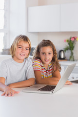 Two children looking at the camera with laptop in front