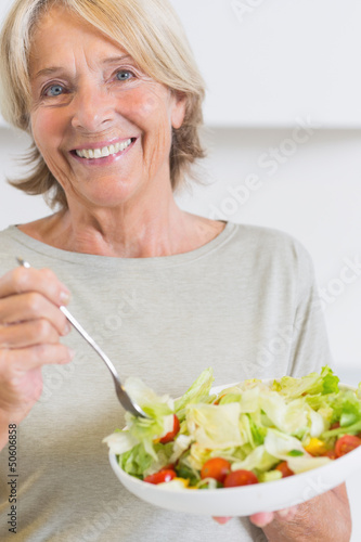 Happy mature woman eating salad