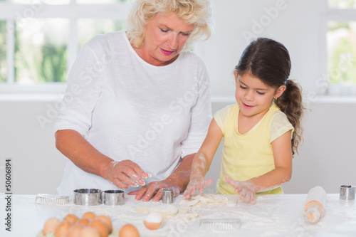 Granddaughter and grandmother preparing cookies together