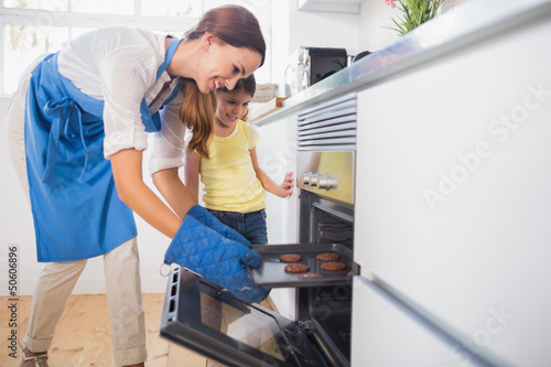 Smiling mother taking cookies out of the oven