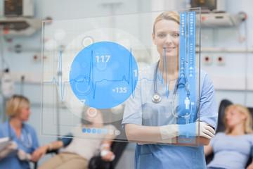Smiling nurse standing behind blue ECG display screen