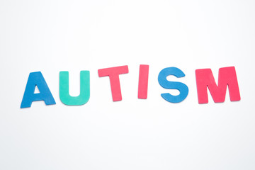 Autism spelled out in pink green and blue