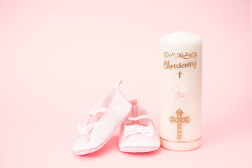 Christening candle with pink baby booties and copy space