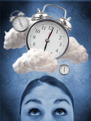 Woman looking up at alarm clock in clouds