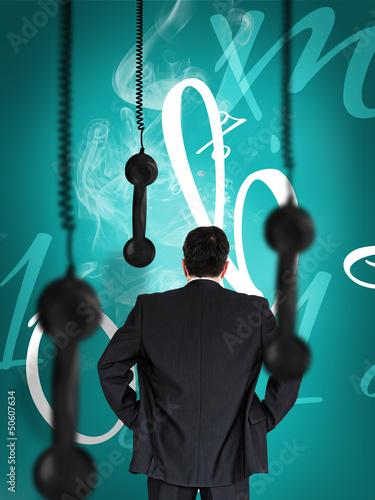 Businessman looking at hanging black telephone receiver