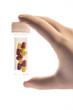 Gloved hand holding a jar of medicine