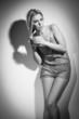 Glamorous young woman near white wall