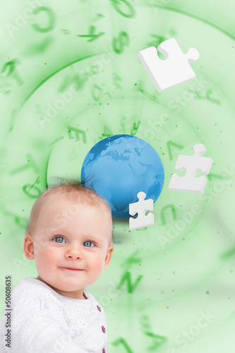 Portrait of a baby with planet and jigsaw pieces green backgroun