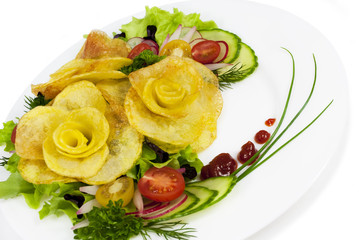 French fries in the form of a rose on a plate with a salad on wh