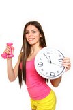Attractive young woman with a clock and dumbbells on a white bac