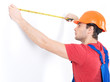 Construction worker measuring the wall