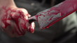 Close up of man gripping bloody knife with blood dripping