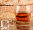 Glass of whiskey and ice on brick wall background