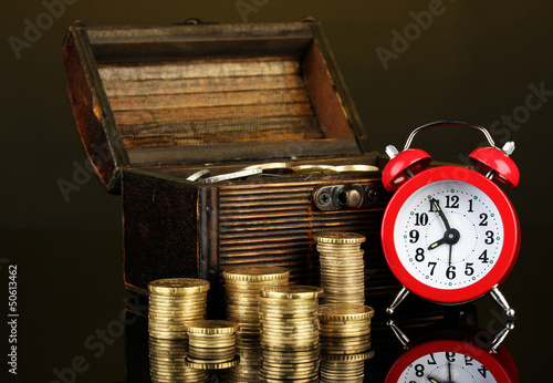 Alarm clock with coins in chest on dark background