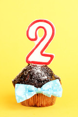 Birthday cupcake with chocolate frosting on yellow background