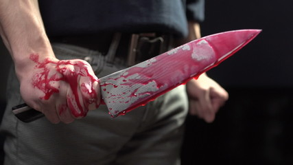 Man holding bloody knife, trembling in shock