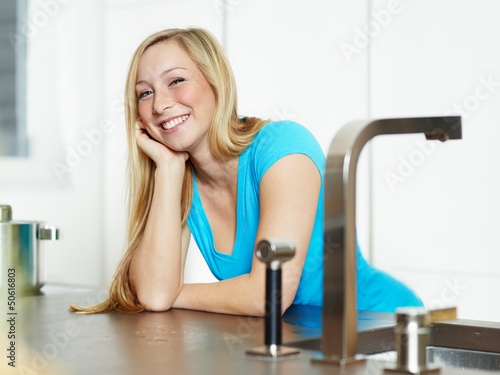 Smiling young woman stands at the kitchen counter