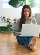Young Woman Sitting On Floor And Using Laptop