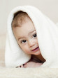 Happy smiling baby under a white towel