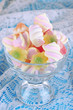 Gentle marshmallow in glass vase on wooden table close-up