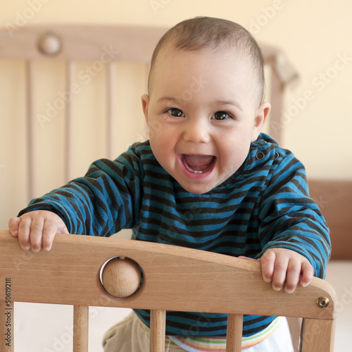 Happy baby standing in cot