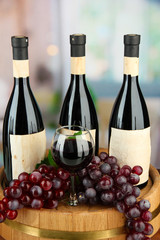 Composition of wine bottles, glass and  grape,on wooden barrel,