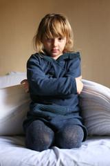 Bambina triste sul letto