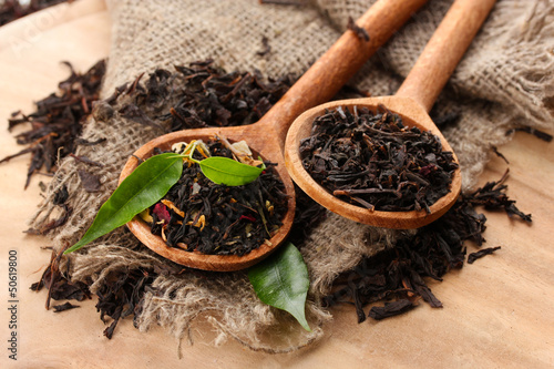 Dry tea with green leaves in wooden spoons, on wooden