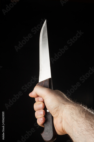 Hairy male hand  holding a knife over a black background