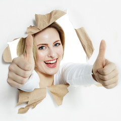 Pretty woman with thumbs up smiling through paper hole