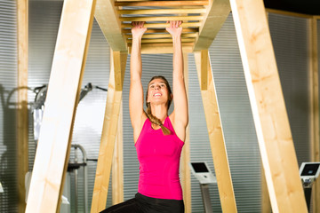 Woman hanging at high or horizontal bar