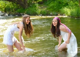 Zwei junge Mädchen albern im Fluss herum